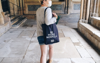 Be More Noroflk this Norfolk Day. Steph at Norwich Cathedral carrying our Be More Norfolk organic cotton tote bag.